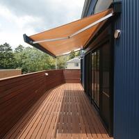 2.7mほど突き出た広い木製デッキにオレンジ色のオーニングが、よく似合うの画像