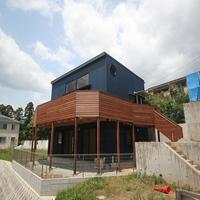 青いガルバリウム鋼板の外壁と木製デッキの似合う外観の画像