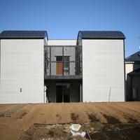 建物西側は2階デッキに設けた縦格子が印象的な外観に仕上がっている の画像