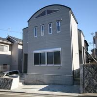 道路から一段高い敷地に建つ建物は、丸い屋根が印象的な家となりましたの画像