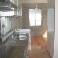 コンクリートの質感に合わせて選んだステンレス製キッチンの画像