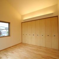 寝室に設けた大きな収納と適度な灯りをもたらす照明の画像