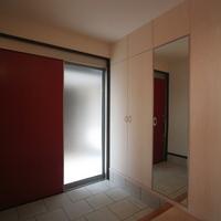 赤い引き戸が印象的な玄関には広い収納とベンチの設えの画像