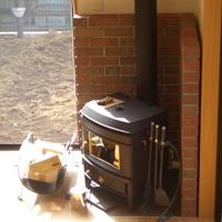 居間に設けられた小さな薪ストーブが家全体を暖めてくれるの画像