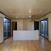 シンプルなアイランド型キッチンが居間の中心に座る。家族が何処を中心に集うのかを明確にするの画像