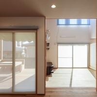 キッチンから居間を眺めると手前の窓の外には木製デッキが見えるの画像